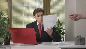 Il giovane capo non gradisce il rapporto, non schiaccia il documento e non lo getta in un impiegato secondario 60 fps stock footage