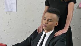 Il giovane capo si avvicina a e flirta con un giovane impiegato sorridente africano, delicatamente tocca le sue spalle, massaggi archivi video
