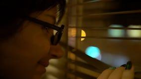 Il giovane castana con i vetri con un orlo nero spinge i ciechi con la sua mano con un manicure esamina la finestra e fotografia stock libera da diritti