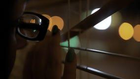 Il giovane castana con i vetri con un orlo nero spinge i ciechi con la sua mano con un manicure esamina la finestra immagini stock