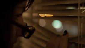 Il giovane castana con i vetri con un orlo nero spinge i ciechi con la sua mano con un manicure esamina la finestra fotografia stock