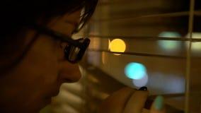 Il giovane castana con i vetri con un orlo nero spinge i ciechi con la sua mano con un manicure esamina la finestra immagini stock libere da diritti