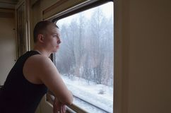 Il giovane caucasico fa una pausa la finestra in un vagone e gli sguardi alla finestra su un paesaggio innevato dell'inverno fotografie stock libere da diritti