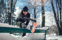 Il giovane che allunga la gamba sull'inverno della neve condiziona Fotografie Stock