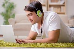 Il giovane che ascolta la musica dal computer portatile Immagine Stock