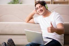 Il giovane che ascolta la musica dal computer portatile Fotografia Stock