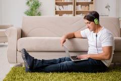 Il giovane che ascolta la musica dal computer portatile Fotografie Stock