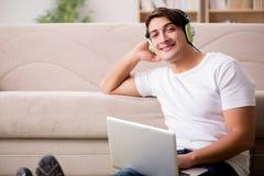 Il giovane che ascolta la musica dal computer portatile Fotografie Stock Libere da Diritti