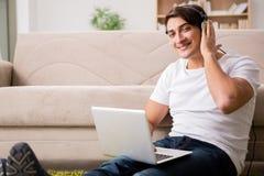 Il giovane che ascolta la musica dal computer portatile Immagini Stock