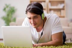 Il giovane che ascolta la musica dal computer portatile Fotografia Stock Libera da Diritti