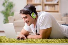 Il giovane che ascolta la musica dal computer portatile Immagini Stock Libere da Diritti