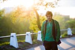 Il giovane che cammina intorno alla città che ascolta la musica con le cuffie dell'orecchio esamina la macchina fotografica in la Immagini Stock Libere da Diritti