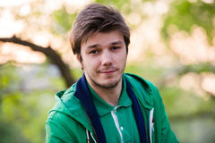 Il giovane che cammina intorno alla città che ascolta la musica con le cuffie dell'orecchio esamina la macchina fotografica in la Fotografia Stock Libera da Diritti