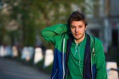 Il giovane che cammina intorno alla città che ascolta la musica con le cuffie dell'orecchio esamina la macchina fotografica e sor Immagine Stock