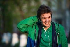 Il giovane che cammina intorno alla città che ascolta la musica con le cuffie dell'orecchio esamina la macchina fotografica e sor Immagini Stock Libere da Diritti