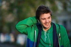 Il giovane che cammina intorno alla città che ascolta la musica con le cuffie dell'orecchio esamina la macchina fotografica e sor Fotografia Stock Libera da Diritti
