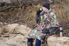 Il giovane che cammina sulla spiaggia congelata in un impermeabile militare beve il tè caldo Fotografia Stock Libera da Diritti