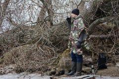 Il giovane che cammina sulla spiaggia congelata in un impermeabile militare beve il tè caldo Fotografia Stock