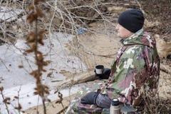 Il giovane che cammina sulla spiaggia congelata in un impermeabile militare beve il tè caldo Fotografie Stock
