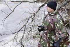 Il giovane che cammina sulla spiaggia congelata in un impermeabile militare beve il tè caldo Immagine Stock Libera da Diritti