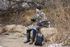 Il giovane che cammina sulla spiaggia congelata in un impermeabile militare beve il tè caldo Fotografie Stock Libere da Diritti