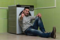 Il giovane che fa i pollici della lavanderia di lavoro domestico aumenta il segno fotografia stock