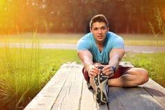 Il giovane che fa l'allungamento dell'esercizio mette in mostra il wor di forma fisica di addestramento Fotografia Stock Libera da Diritti