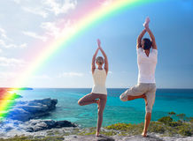 Il giovane che fa l'yoga si esercita sulla spiaggia dell'estate Immagine Stock Libera da Diritti