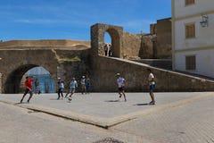 Il giovane che gioca a calcio in un quadrato vicino alle pareti della fortezza della città portoghese cita Portugaise nella città immagini stock
