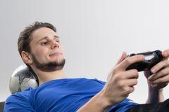 Il giovane che gioca i video giochi in camicia nera ha isolato lo studio Fotografie Stock