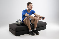 Il giovane che gioca i video giochi in camicia nera ha isolato lo studio Immagine Stock