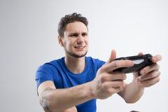 Il giovane che gioca i video giochi in camicia nera ha isolato lo studio Fotografie Stock Libere da Diritti