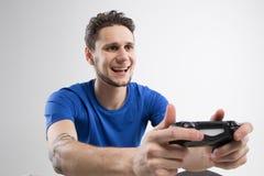 Il giovane che gioca i video giochi in camicia nera ha isolato lo studio Immagini Stock