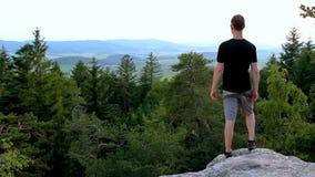 Il giovane che guarda alla valle da roccia, si rilassa nel paesaggio archivi video