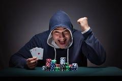 Il giovane che indossa una maglia con cappuccio con le carte ed i chip che giocano Fotografia Stock Libera da Diritti