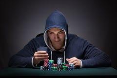 Il giovane che indossa una maglia con cappuccio con le carte ed i chip che giocano Immagine Stock