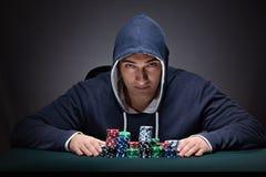 Il giovane che indossa una maglia con cappuccio con le carte ed i chip che giocano Fotografie Stock