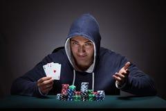 Il giovane che indossa una maglia con cappuccio con le carte ed i chip che giocano Fotografia Stock