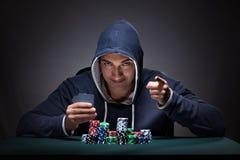 Il giovane che indossa una maglia con cappuccio con le carte ed i chip che giocano Immagini Stock Libere da Diritti