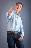 Il giovane che mostra i pollici aumenta il segno Fotografia Stock Libera da Diritti