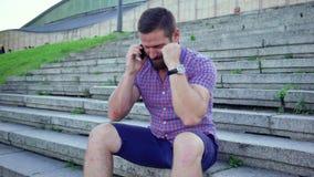 Il giovane che parla dallo smartphone riceve le informazioni molto buone stock footage