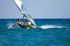 Il giovane che pratica il surfing il vento dentro spruzza dell'acqua Fotografia Stock