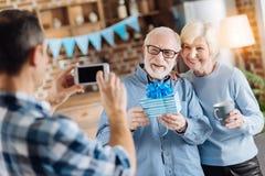 Il giovane che prende la foto dei suoi anziani parents il regalo della tenuta immagini stock libere da diritti