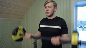 Il giovane che risolve le sue mani che di sollevamento i dumbels ed esercita il suo bicipite archivi video