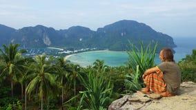 Il giovane che si rilassa su una roccia in Tailandia dal phi del phi di Ko indossa il punto di vista dell'isola Immagini Stock