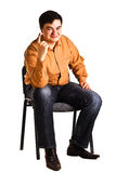 Il giovane che si siede su una presidenza mostra la barretta Immagine Stock Libera da Diritti