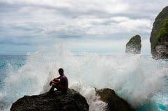 Il giovane che si siede sulla roccia con il mare ondeggia irrompendo la parte anteriore Fotografia Stock