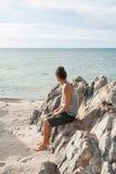Il giovane che si siede sulla spiaggia e considera la linea di orizzonte Fotografia Stock Libera da Diritti