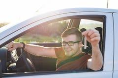 Il giovane che sorride e che tiene digita la sua automobile Concetto automatico della gente e dell'acquisto Immagine Stock