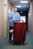 Il giovane che spinge un carretto del governo della casa caricato con gli asciugamani puliti, la lavanderia e le attrezzature per Fotografia Stock Libera da Diritti
